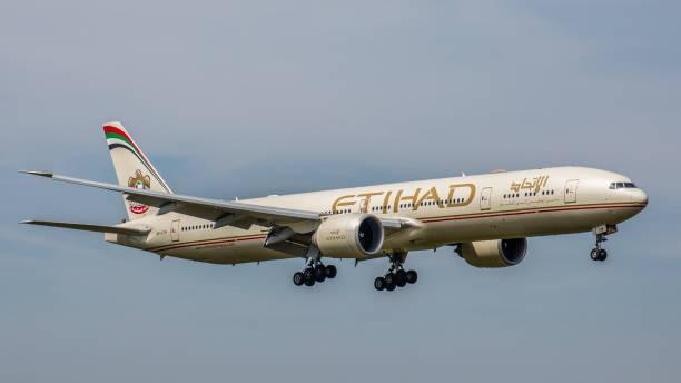 boeing 777 etihad airways nähert sich dem flughafen münchen - andreas haas stock-fotos und bilder