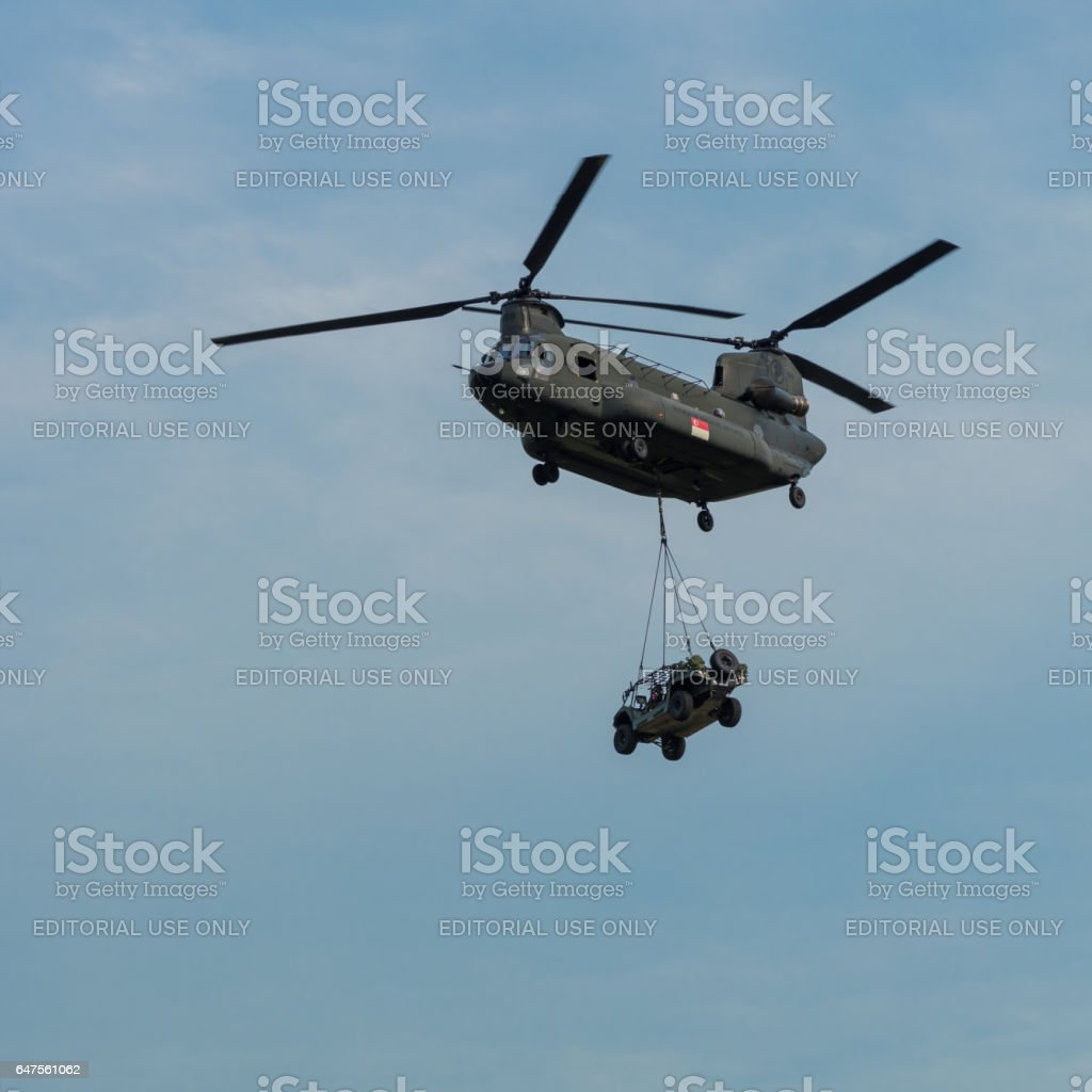 RSAF Boeing Chinook helicopter lifting utility vehicle stock photo