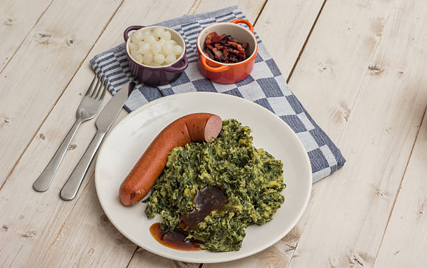 boerenkool with smoked sausage and bacon on a white plate - stamppot stockfoto's en -beelden