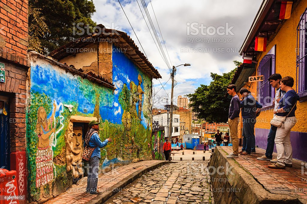 Bogotá, Colombia - A Tour Guide Explains A Legend To Tourists on the Narrow, Colorful, Cobblestoned Calle del Embudo In The Historic La Candelaria District - foto de stock