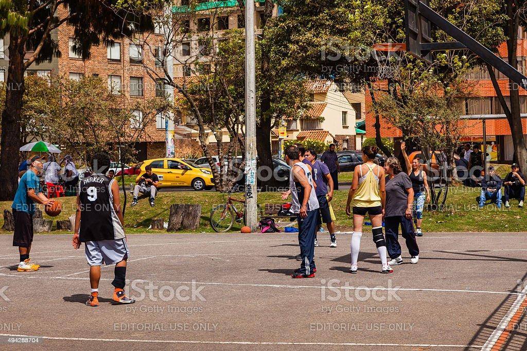 Bogotá, Colombia - Friends enjoy basketball at roadside public park stock photo