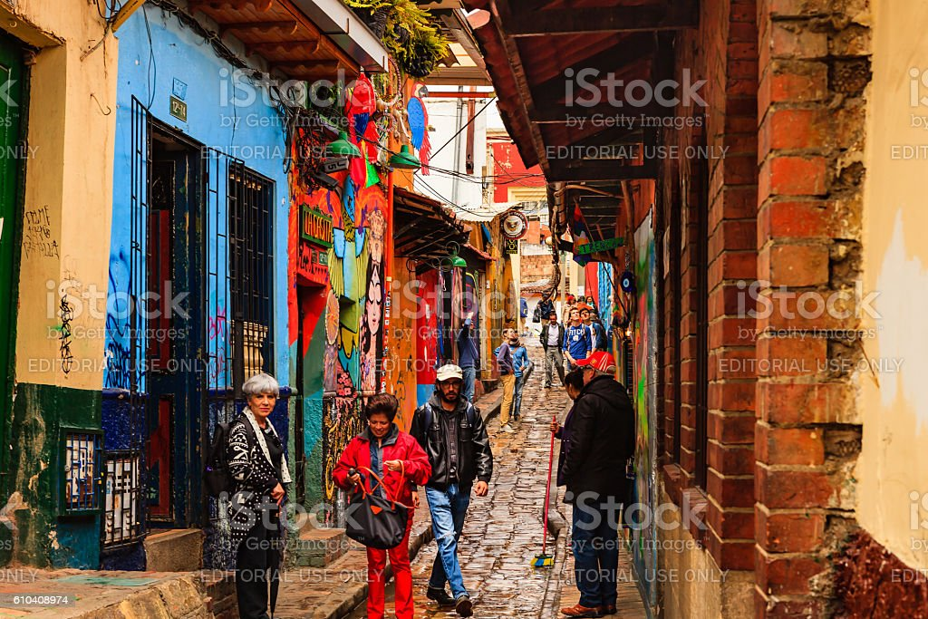 Bogotá, Colombia - Local Colombian Tourists Walk Through The Narrow, Colorful, Cobblestoned Calle del Embudo In The Historic La Candelaria District - foto de stock