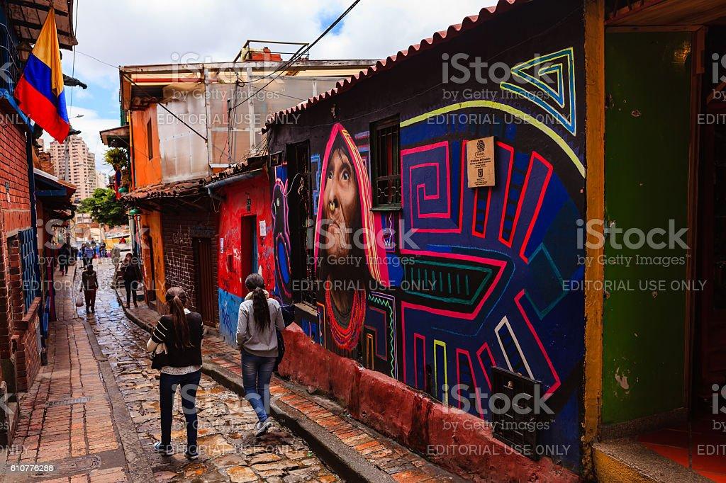 Bogotá, Colombia - Local Colombians Walk Through The Narrow, Colorful, Cobblestoned Calle del Embudo In The Historic La Candelaria District stock photo