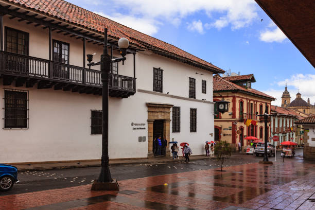 Bogotá Colombia - Looking across Calle 11 in the La Candelaria District, towards the entrance to the Casa de Moneda. Rain and Spanish Colonial Architecture Bogotá, Colombia - July 20, 2016: Looking down Calle 11 in the historical La Candelaria district of Bogotá, the Andean capital city of the South American country of Colombia. It has just started to rain so people walking on the street are using umbrellas. The sky just about a kilometre down the road is blue and obviously no rain downhill. Across the street in the entrance to the Casa de Moneda, which used to be the country's mint in colonial times but is today, a Museum dedicated to coinage. Down the road are also a couple of vendors selling street food. It is 20th July, National Day and a holiday in Colombia; the streets are therefore not as busy as they can normally be. Photo shot on a cloudy afternoon; horizontal format. Copy space. chandra dhas, stock pictures, royalty-free photos & images