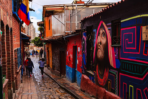 Bogotá, Colombia - People Walk Through The Narrow, Colorful, Cobblestoned Calle del Embudo In The Historic La Candelaria District stock photo