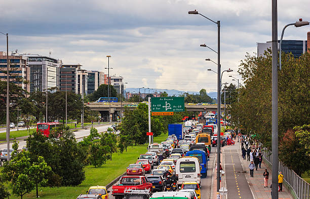 Bogotá, Colombia -  Trancón  on Avenida El Dorado Bogota, Colombia - September 11, 2015: The Avenida El Dorado that runs from the East of the City to the West; from downtown Bogota, to the International Airport. Photo shows a trancón or traffic jam in the lanes that will join the Avenida. Bicycle lanes and people can be seen on the sidewalk. Photo shot in the afternoon sunlight; horizontal format. Copy space. bus rapid transit stock pictures, royalty-free photos & images