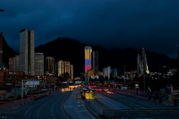 Bogota cityscape at night time BOGOTA,COLOMBIA-JUNE 26,2016: Cityscape at night time of buildings and streets of Bogota,Colombia. On the Background the Colpatria Tower Building is iluminated with led lights. bus rapid transit stock pictures, royalty-free photos & images