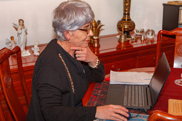 Bogota, Colombia - A Senior Gray Haired Latin American Lady Is Working From Home On Her Laptop Computer Set Up On A Rosewood Dining Table; She Has Notes By Her Side. stock photo