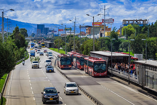 Bogota, Colombia - Autopista Norte and Transmilenio Bogota, Colombia - December 05, 2013:  Looking to the South of the capital city of Bogota in Colombia, South America, at the northbound carriageway of the Autopista Norte.  To the right of the photo is the TransMilenio station Calle 146; several articulated buses can be seen; they have their own lanes on the carriageway reserved solely for their own use.  The station is crowded with embarking and disembarking passengers.  The other lanes carry normal traffic.  In the far background is visible the Andes Mountains. Photo shot in the morning sunlight; horizontal format. bus rapid transit stock pictures, royalty-free photos & images