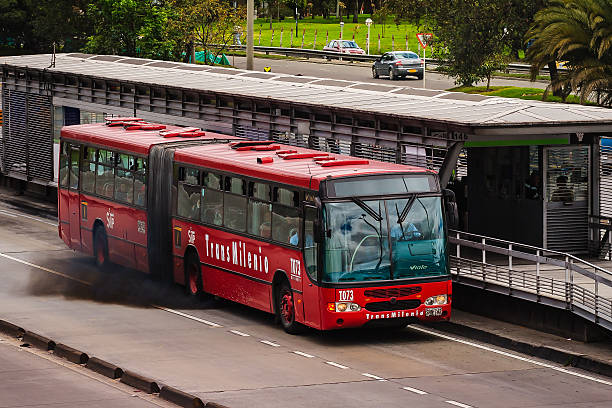 Bogota, Colombia - Black Exhaust Fumes From A Public Transportation, Articulated Bus Pollutes The Clean Air Of the Andes Mountains - An Illegal Pollutant. Bogota, Colombia - July 20, 2015: A TransMilenio articulated bus pulls out of the Calle 146 Station in the capital city of Bogota in Colombia, South America, on the northbound carriageway of the Autopista Norte.  Unacceptable levels of pollution can be seen from the exhaust of the bus. The TransMilenio is the capital city's Bus Rapid Transport system.  Bogota is situated on the Andes Mountains, at a level of 8500 feet above mean sea level; at such an elevation the air should be clean and healthy. Photo shot in the Afternoon sunlight; horizontal format. Copy space. bus rapid transit stock pictures, royalty-free photos & images