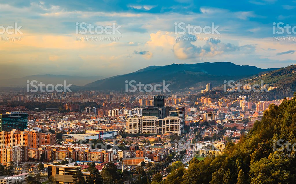 Bogota, Colombia: High Angle View Of Bario de Usaquén From The Heights Of La Calera On The Andes Mountains At Sunset Time The Barrio de Usaquen viewed from the heights of La Calera in  the capital city of Bogota, Colombia in South America at sunset time.  The setting sun hits the buildings both tall and small at an oblique angle.  The road that can be seen in the foreground is Carrera Septima; traffic is congested because offices have just closed.  To the left of the photo is some smog. In the distance, are the always present Andes Mountains.  Horizontal format; copy space. 2015 Stock Photo