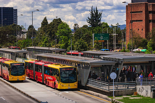 Bogota, Colombia: The El Salitre TransMilenio Station On Calle 26 Or Avenida El Dorado With Typical Articulated Busses Bogotá, Colombia - September 22, 2015: The Salitre El Greco TransMilenio station on Avenida El Dorado that runs from the East of the capital City, to the West; from downtown Bogotá, to the International Airport. The two articulated busses on the lower section of the photo are coming from the Airport side and going to the centre of the city. People can be seen getting off from the busses and leaving the station. In the far background, the always present Andes mountains can be seen. Photo shot in the afternoon sunlight; horizontal format. bus rapid transit stock pictures, royalty-free photos & images
