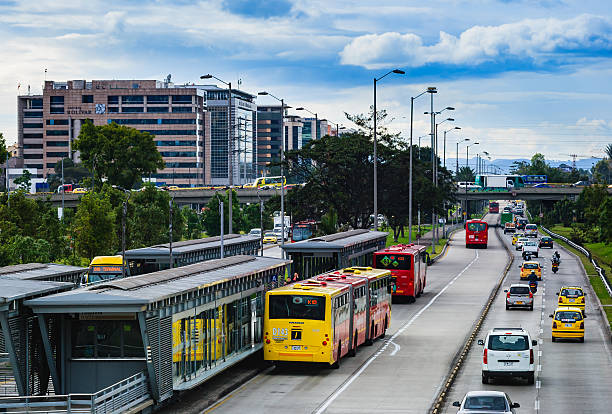 Bogota, Colombia: TransMilenio Station On Calle 26 Or Avenida El Dorado - Carriageway Leading To El Dorado International Airport Bogota, Colombia - September 11, 2015: The Avenida El Dorado that runs from the East of the City to the West; from downtown Bogota, to the International Airport.  Photo shot in the afternoon sunlight on a cloudy day, shows the TransMilenio lanes and the two fast lanes going to the Airport; horizontal format. Copy space. bus rapid transit stock pictures, royalty-free photos & images