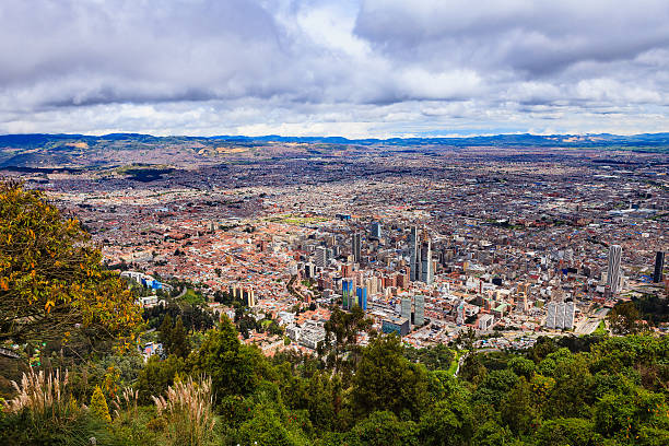 Bogota, Colombia - view of capital city downtown from Monserrate Bogota, Colombia - Looking at the Andean capital city of Bogota, Colombia in South America, from the mountain peak called Monserrate. The red terracotta roof tiled buildings to the left of the image are located in La Candelaria which is the oldest and historic part of the city. The area has many buildings in the colonial Spanish style of architecture. Bogota, located at about 8500 feet above mean sea level, is one of the largest cities in Latin America. On view is a small section of the vast Altiplano Cundiboyacense. Photo shot in the morning sunlight.  Horizontal format. chandra dhas, stock pictures, royalty-free photos & images