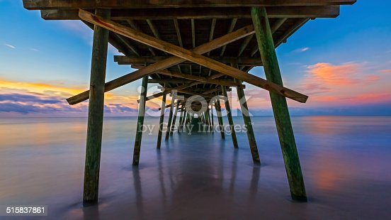 The rising sun paints the sky over the sea with vivid colors as seen from beneath the Bogue Inlet Fishing Pier in Emerald Isle, North Carolina.
