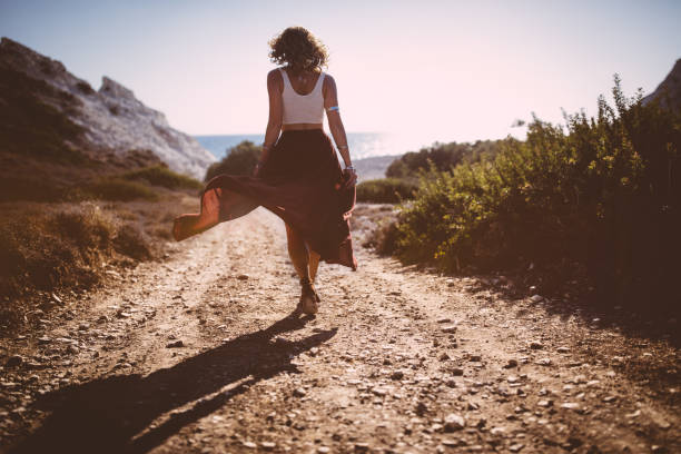 Bohemian girl in skirt and crop top walking in nature stock photo