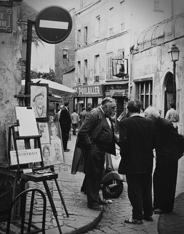 Paris, October 1957 - A group of Bohmian men talking on the sidewalk the Cartier Latin.