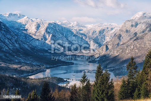 Unusual high angle view on freezing Bohinj lake on sunny winter day. In background snowcapped mountain range of Julian Alps with Mt. Triglav in distance.