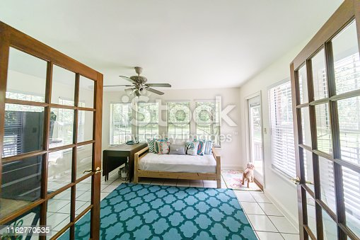 Boho Bohemian style futon seating area with white cushions and colorful pillows and lots of windows and natural light