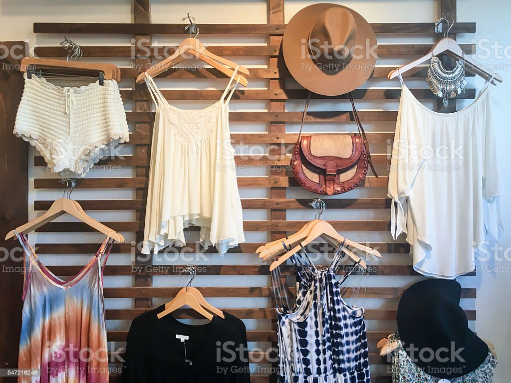 Boho Chic Women's clothing and accessories hanging on wall stock photo