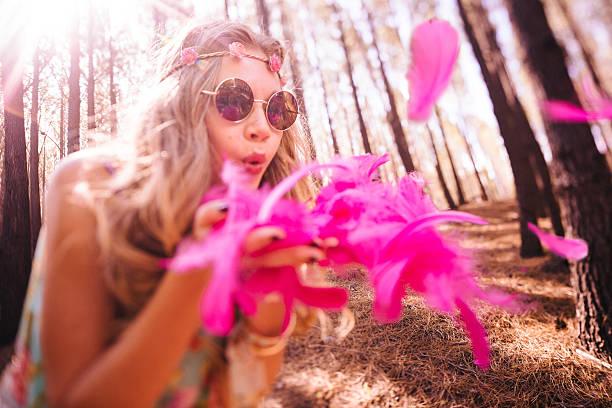 boho-stil mädchen blasen hellen rosa federn - hippie stirnbänder stock-fotos und bilder