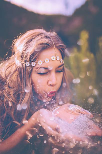 boho-stil mädchen blasen silver glitter in der natur - hippie stirnbänder stock-fotos und bilder