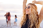 Blonde boho girl raises arms up and smiles enthusiastically in the middle of hipster multi-ethnic group dancing together and moving in front of the ocean on a sandy beach during sunset