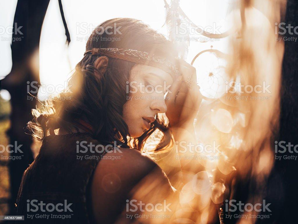 Boho girl in golden sun flare with dreamcatcher stock photo