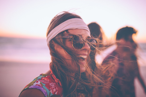 Boho Girl In Sunglasses Laughing On A Beach With Friends Stock Photo - Download Image Now