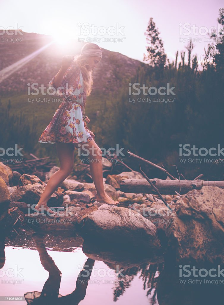 Boho girl in vintage dress stepping over stones at lake stock photo