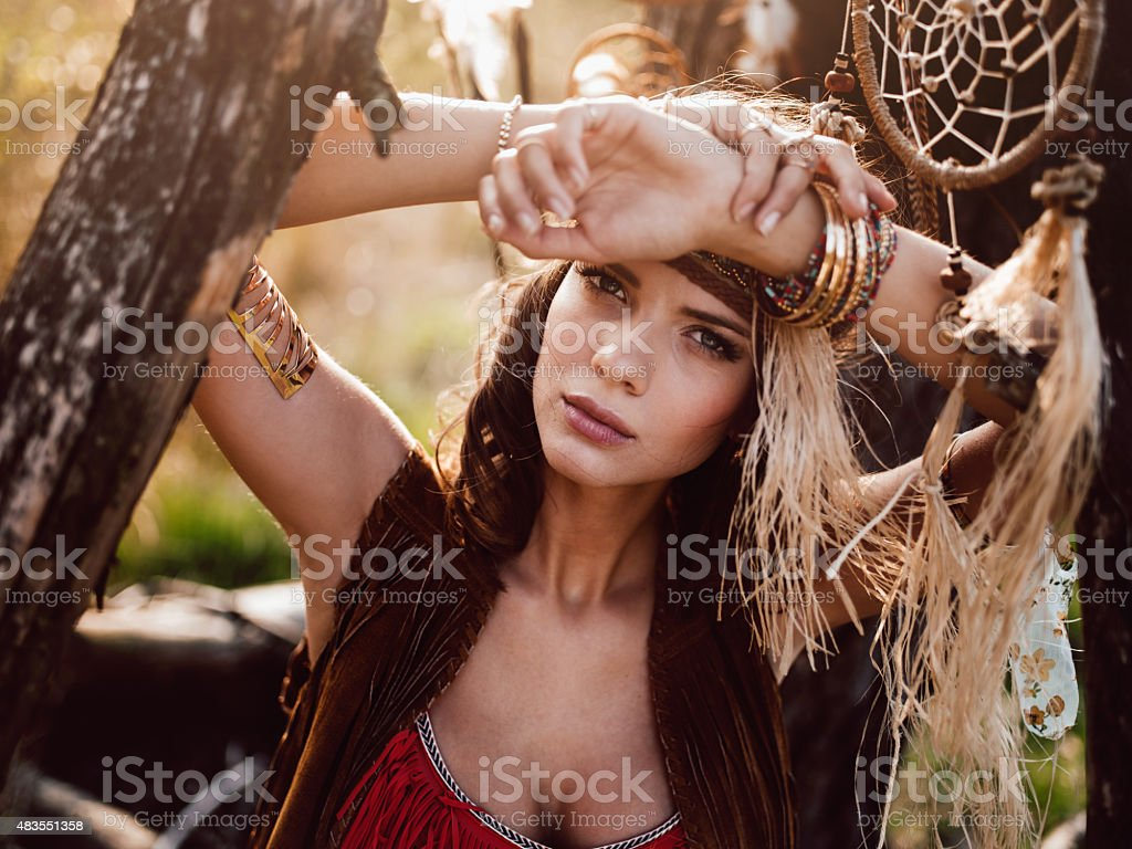 Boho girl looking serious outdoors in the wilderness stock photo
