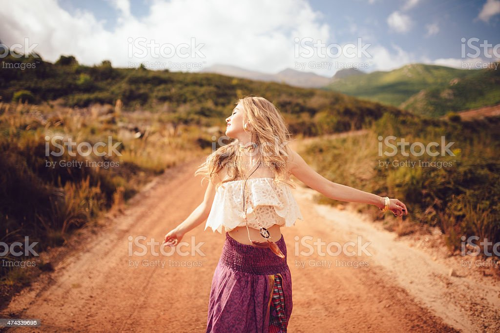 Boho girl on a country dirt road being joyful stock photo