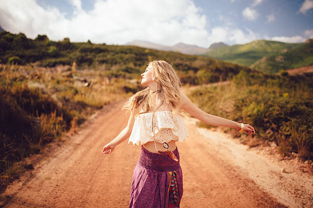 boho girl on a country dirt road being joyful - hippie fashion stock photos and pictures