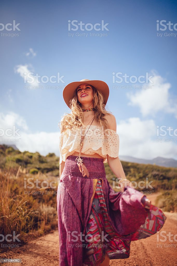 Boho girl on a dirt road in a purple skirt stock photo