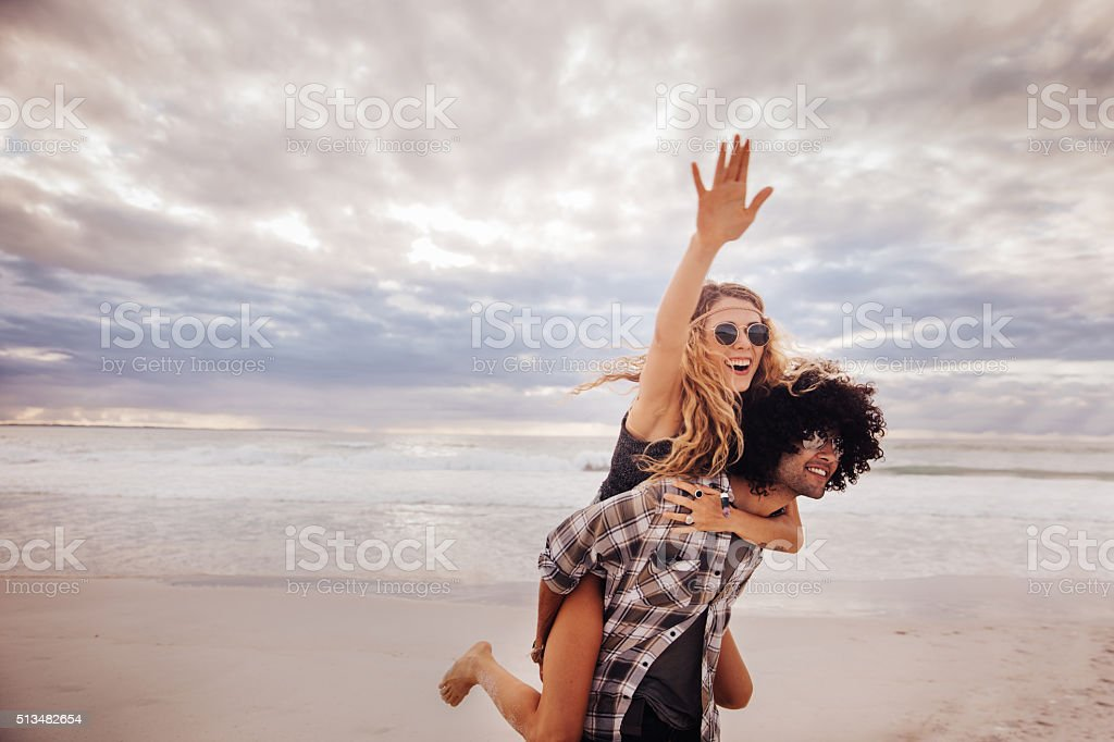Boho Girl Rides Piggyback on hipster Man at Beach stock photo
