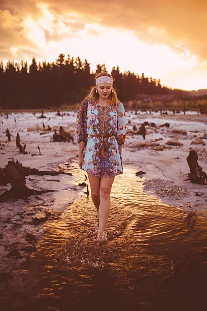 boho-stil mädchen zu fuß in einem see bei sonnenuntergang - hippie kleider stock-fotos und bilder