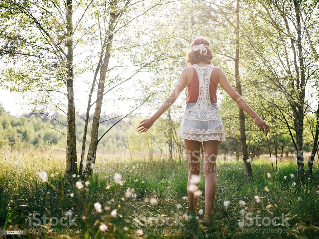 Boho girl walking through summer park feeling free stock photo
