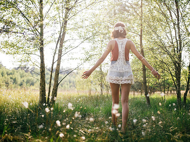 boho girl walking through summer park feeling free - hippie fashion stock photos and pictures