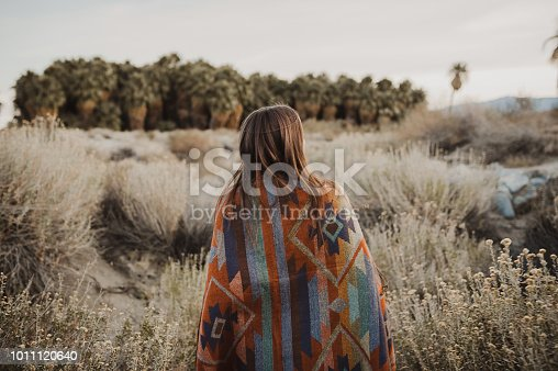 Back side of boho woman in the desert nature.  Artistic photo of young hipster traveler girl in gypsy look,