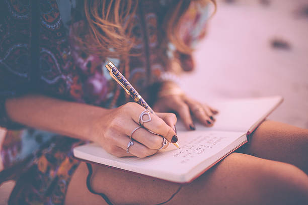 Boho girl writing in her diary wearing a floral dress stock photo