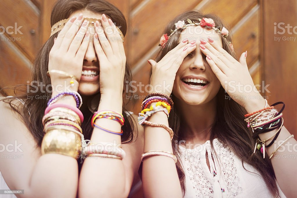Boho girls covering eyes by hands stock photo