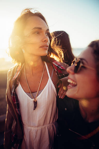Boho girls having fun at beach with friends stock photo