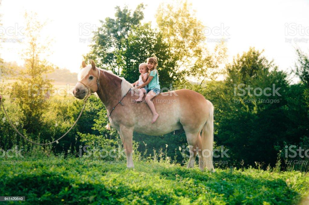 Boho Geschwister Mädchen auf einem Pferd – Foto