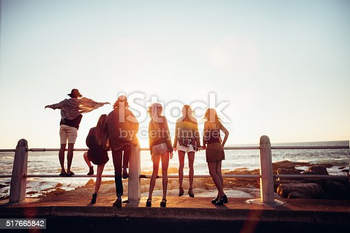 Back view of boho style friends admiring the sea from the promenade with sunset sun flare
