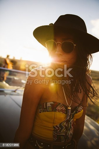 Portrait of a boho style girl wearing a black hat and sun glasses standing outdoors close to a convertible car with afternoon sun flare