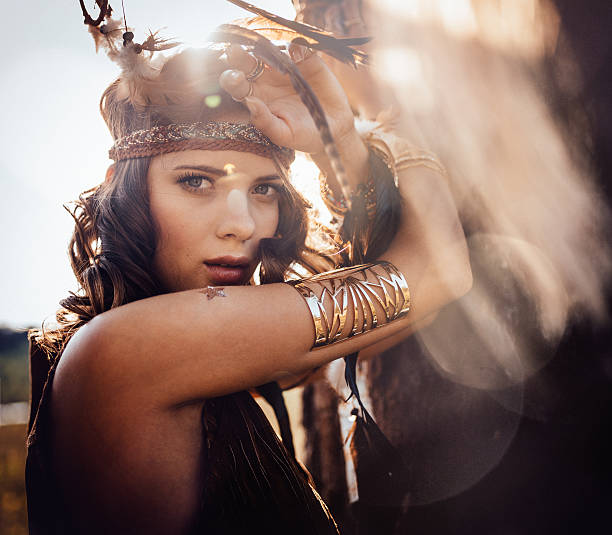 Boho style girl outdoors with sun flare Portrait of a boho style girl wearing a leather headband standing outdoors in nature with afternoon sun flare romani people stock pictures, royalty-free photos & images