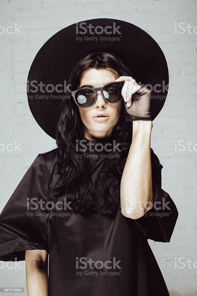 Boho style woman in studio staying near brick wall royalty-free stock photo