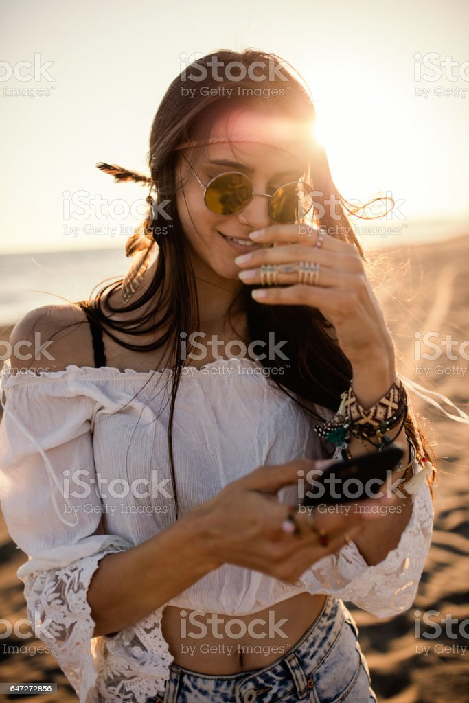 Boho styled woman using her phone on the beach стоковое фото