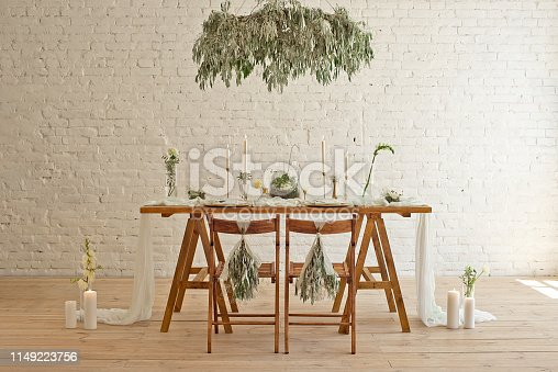 istock Boho wedding table setting, rustic decorations, gold and blue details, wooden table, bokeh. Luxury wedding decor. Monstera leaves and orchid flowers 1149223756