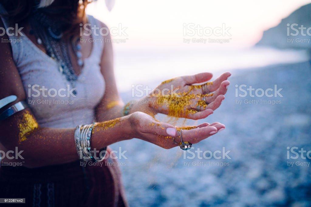 Boho femme sur la plage avec des paillettes d'or sur les mains - Photo